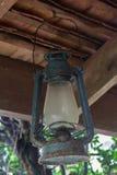 A lâmpada de furacão azul velha pendurada no feixe foto de stock