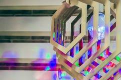 Lâmpada de madeira com um fulgor colorido e destaques na parede fotografia de stock