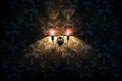 A lâmpada de parede incandesce na parede com papel de parede fotos de stock