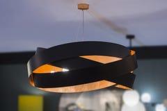 Lâmpada de pendente sob a forma dos anéis, feitos do metal preto e alaranjado Candelabro de cobre e de bronze, lâmpada bonita do  fotos de stock royalty free