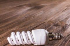 Lâmpada de poupança de energia em um fundo de madeira Foto de Stock