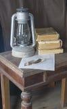 Lâmpada de querosene do envelhecimento com o livro e a pena a descansar em cima de Ta de madeira Imagem de Stock Royalty Free