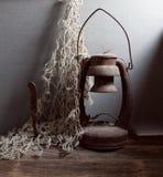 Lâmpada de querosene, faca e rede de pesca oxidadas velhas Fotografia de Stock Royalty Free