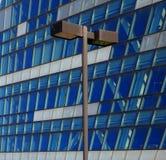 Lâmpada de rua na frente de uma construção de vidro Fotos de Stock