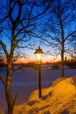 Lâmpada de rua velha iluminada na paisagem do inverno Foto de Stock Royalty Free