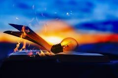 A lâmpada descansa em um livro aberto, conhecimento é luz, o livro está no fogo Foto de Stock Royalty Free
