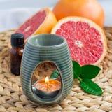 Lâmpada do aroma com óleo essencial da toranja na esteira tecida, toranjas no fundo, formato quadrado fotografia de stock