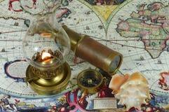 Lâmpada do telescópio pequeno, do compasso, da concha do mar e de querosene Fotografia de Stock Royalty Free