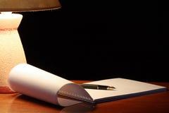 Lâmpada e caderno espiral Fotografia de Stock Royalty Free