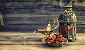 Lâmpada e datas da ramadã no fundo de madeira Lanterna oriental Foto de Stock