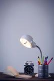 Lâmpada elétrica iluminada com o organizador da mesa pelo livro e pelo despertador Foto de Stock Royalty Free