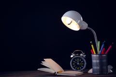Lâmpada iluminada com o organizador da mesa pelo despertador e pelo livro Fotografia de Stock Royalty Free