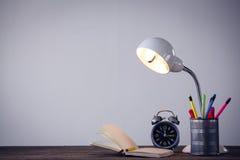 Lâmpada iluminada com o organizador da mesa pelo livro e pelo despertador Imagem de Stock