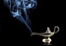 Lâmpada mágica no fundo preto da história de Aladdin com os gênios que aparecem no conceito azul do fumo para o desejo, a sorte e Foto de Stock