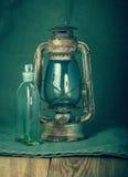 Lâmpada oxidada e uma garrafa do querosene Fotografia de Stock Royalty Free