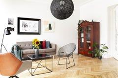 Lâmpada preta acima da poltrona e da tabela no interior brilhante da sala de visitas com cartaz e plantas Foto real fotografia de stock