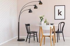 Lâmpada preta acima das cadeiras e tabela de madeira com as flores na sala de jantar interior com cartaz Foto real imagens de stock