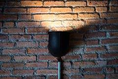 Lâmpada preta com luz na textura da parede de tijolo foto de stock