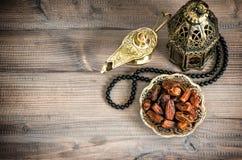 Lâmpada, rosário e datas da ramadã no fundo de madeira Fotos de Stock Royalty Free
