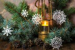 Lâmpada velha com vela ardente em ramos de árvore do Natal Imagens de Stock