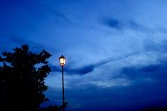 A lâmpada velha iluminou-se, silouette da árvore, e céu azul na hora azul Fotos de Stock Royalty Free