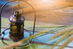 A lâmpada velha na tabela com grama floresce Fotografia de Stock Royalty Free