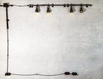 Lâmpadas de pendente industriais contra a parede áspera, estilo do sótão os fios e os soquetes pretos em torno do perímetro criam imagens de stock royalty free
