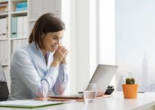 Lächelnde Geschäftsfrau, die an ihren Laptop arbeitet und anschließt lizenzfreie stockfotografie