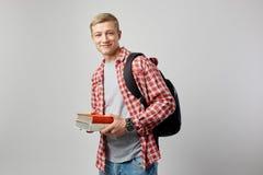 Lächelnder junger blonder Kerl mit schwarzem Rucksack auf seiner Schulter gekleidet in einem weißen T-Shirt, in einem roten karie stockfoto