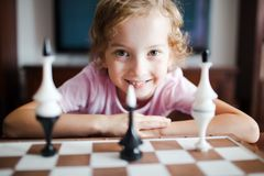Lächelndes Kind und Schachfiguren stockfoto