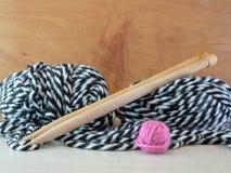 Lãs de confecção de malhas em preto e branco com as grandes agulhas de confecção de malhas de madeira Imagem de Stock