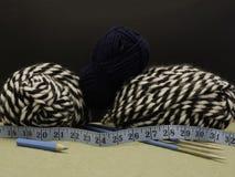Lãs de confecção de malhas em preto e branco E um skein do azul Fotografia de Stock