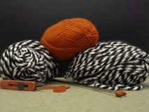 Lãs de confecção de malhas em preto e branco E um skein do vermelho Foto de Stock