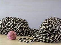 Lãs de confecção de malhas no preto e uma bola cor-de-rosa pequena das lãs Imagens de Stock