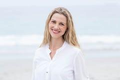 Lächeln blond, das Meer bereitstehend und Betrachten der Kamera Lizenzfreie Stockfotos