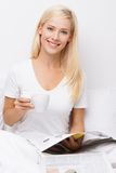 Lächeln blond im Bett mit einem Tasse Kaffee Stockfotos