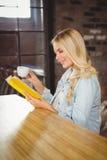 Lächeln blond, Kaffee und Lesebuch habend Stockbilder