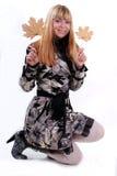 Lächeln blond mit Blättern Stockfoto