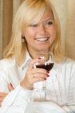 Lächeln blond mit einem Glas Rotwein Stockfotos