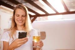 Lächeln blond mit einem Mobiltelefon und einem Bier Lizenzfreies Stockbild