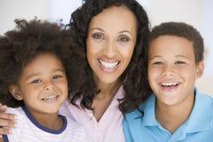 Lächeln der Frau und zwei junger Kinder Stockbild