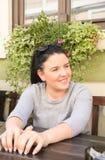 Lächeln der jungen Frau, wartend am Tisch Stockfoto