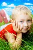 Lächeln des glücklichen netten Grases des Kindes im Frühjahr Stockfotos