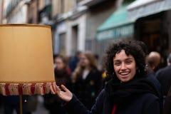 Lächeln des jungen Mädchens, wenn eine Retro- Lampe in einem Antikmarkt betrachtet wird lizenzfreies stockbild