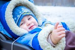 Lächeln des kleinen Jungen Lustiges Baby in einem Wagen Stockfoto