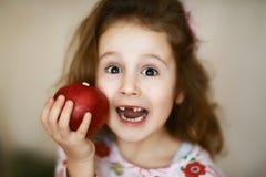 Lächeln eines hält nettes kleines gelocktes zahnlos Mädchens und einen roten Apfel, ein Porträt eines glücklichen Babys, das eine stockfoto