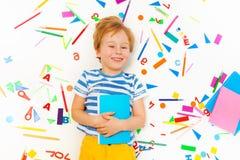 Lächeln fünf Jahre alte Junge, die Lehrbuch halten Lizenzfreie Stockfotografie