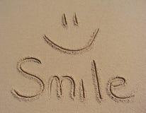 Lächeln geschrieben in den Sand Stockfotos