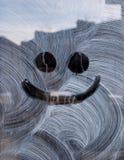 Lächeln gezeichnet auf neue weiße Malerei auf einem Glasfenster stockfotos
