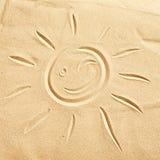 Lächeln, glückliche Sonne auf goldenem Strandsand blinzelnd lizenzfreie stockbilder
